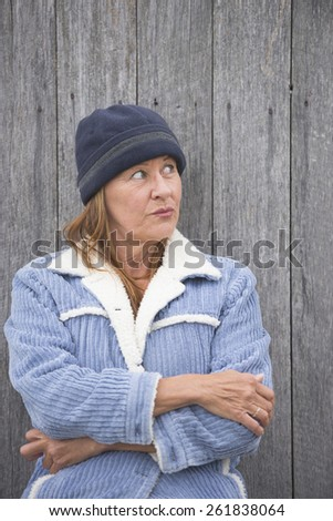 Portrait happy confident smiling attractive mature woman outdoor, wearing warm bonnet and wool jacket, timber wall background. - stock photo
