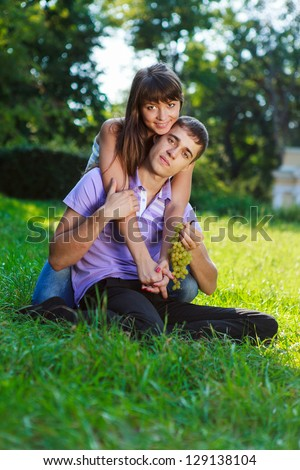 Portrait happy couple with a bunch of grapes in hands in a summer sunny park. Outdoor