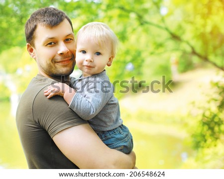 Portrait happy dad and son in summer day - stock photo