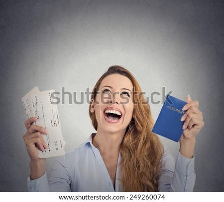 Portrait happy excited tourist young woman holding passport holiday flight ticket looking up isolated grey wall background. Positive human emotion face expression. Travel vacation getaway trip concept - stock photo