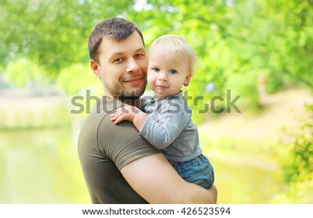 Portrait happy father and son on hands in summer day - stock photo