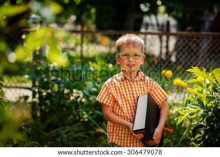 Portrait Happy little boy holding a big book on his first day to school or nursery. Outdoors, Back to school concept - stock photo