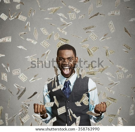 Portrait happy man exults pumping fists ecstatic celebrates success screaming under money rain falling down dollar bills banknotes isolated gray background with copy space. Financial freedom concept   - stock photo