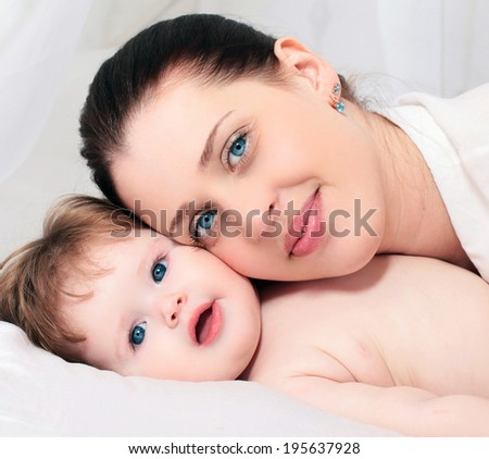 Portrait happy mother and baby on the bed - stock photo
