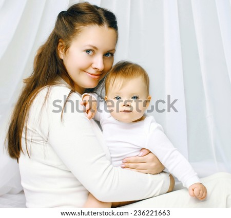 Portrait happy mother and baby on the bed at home