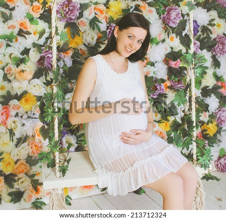 Portrait happy pregnant girl on a background of flowers. female happiness - stock photo