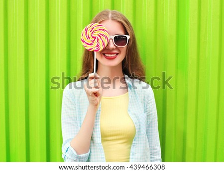 Portrait happy pretty smiling woman and lollipop over colorful green background - stock photo