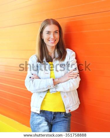 Portrait happy pretty smiling woman over colorful orange background - stock photo