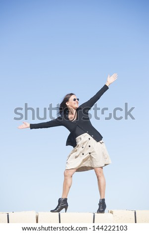 Portrait happy sexy mature woman with arms up, wearing skirt, fishnet stockings and boots, is standing confident, relaxed and joyful on wall, isolated with blue sky as background and copy space.