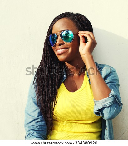 Portrait happy smiling african woman in colorful clothes and sunglasses in profile - stock photo