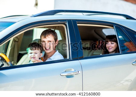Portrait happy, smiling Family, mother, father, kid sitting in the white, silver car looking out windows, ready for vacation trip, outdoor background. Positive Human face expression, emotions