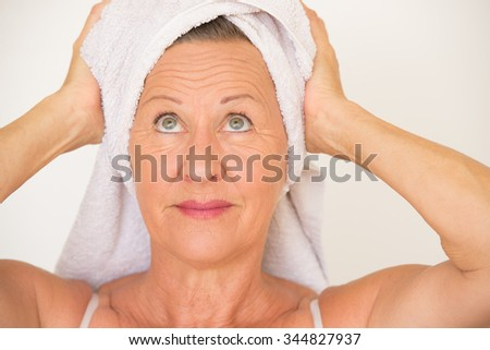 Portrait happy smiling healthy attractive mature woman with white spa towel on head, bright background.