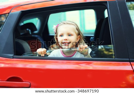 Portrait happy smiling little child sitting in red car