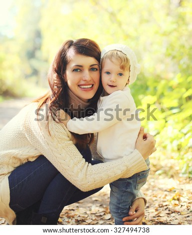 Portrait happy smiling mother and child walking in autumn park - stock photo