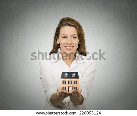 Portrait happy smiling  woman presenting small model of house, isolated grey wall background. Positive human face expressions, emotions, feelings. Real estate, home ownership concept - stock photo