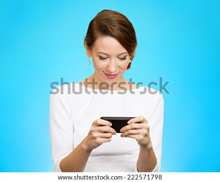 Portrait happy, smiling woman texting on her smart phone, isolated blue background. Communication concept. Positive facial expressions, emotion, feelings, good news. Internet, game, phone addiction - stock photo