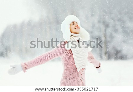 Portrait happy smiling woman wearing a sweater and hat enjoys winter day