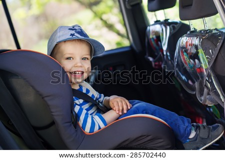 portrait happy toddler boy sitting in the car seat