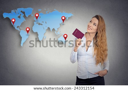 Portrait happy tourist young woman holding passport standing looking at world map planning isolated grey wall background. Positive human emotion face expression. Travel vacation getaway trip concept  - stock photo