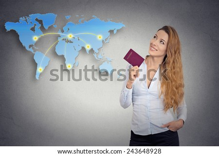 Portrait happy tourist young woman holding passport standing looking at world map planning ready to go isolated grey background. Positive emotion face expression. Travel vacation getaway trip concept - stock photo