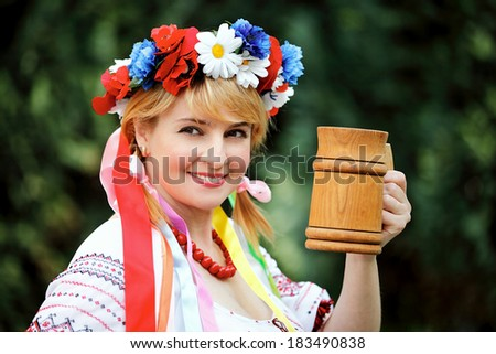 Portrait Happy Ukrainian woman with a wooden mug - stock photo