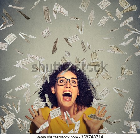 Portrait happy woman in glasses exults pumping fists ecstatic celebrates success under a money rain falling down dollar bills banknotes isolated on gray wall background with copy space   - stock photo