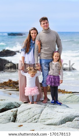 portrait happy young family of four in casual fashion wear on a sandy beach at sunny summer day