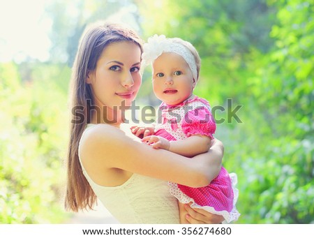 Portrait happy young mother and baby on hands in summer day - stock photo