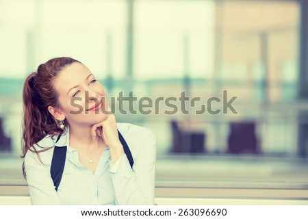 Portrait happy young woman thinking dreaming has many ideas looking up isolated office windows background. Positive human face expression emotion feeling reaction. Decision making process concept - stock photo