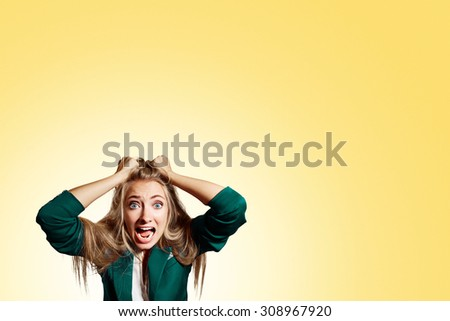 Portrait headshot very sad depressed, stressed disappointed gloomy young man head on hands screaming in despair isolated on yellow wall background. Human emotion facial expression reaction - stock photo