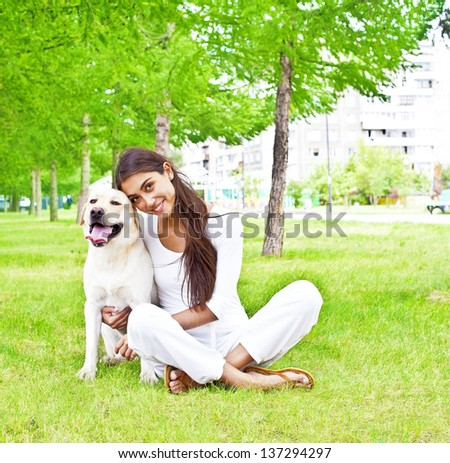 portrait Hispanic girl embracing her dog in the park on the background of the house