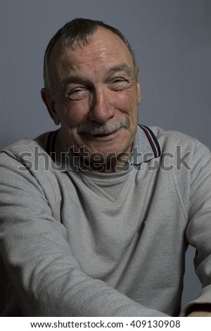 Portrait image of a happy mature man. Studio shot taken on a grey background. - stock photo