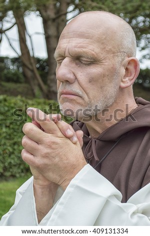 Portrait image of a mature man dressed as a monk, praying in an outdoor setting. - stock photo