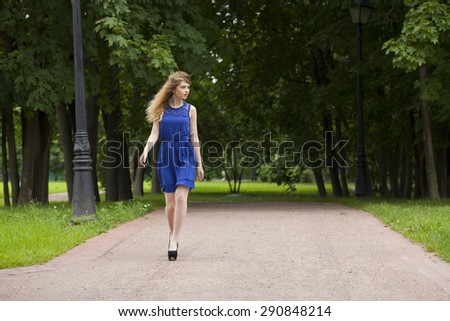 Portrait in full growth, attractive young blonde woman in blue dress walking in summer park