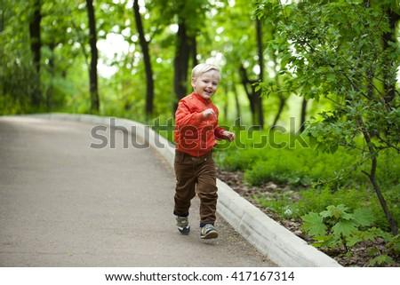 Portrait in full growth, Happy Little boy in orange jacket walking in summer park - stock photo