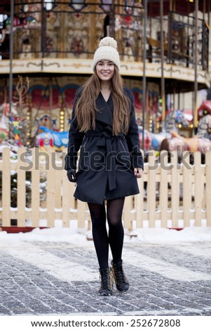 Portrait in full growth of a beautiful young brown haired woman on the background of a winter amusement park - stock photo