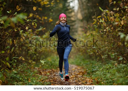 Portrait in full growth of sporty woman jogging in park