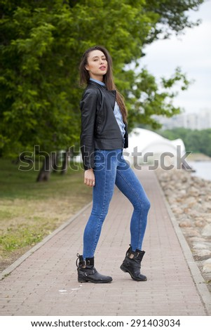 Portrait in full growth the young beautiful girl in blue jeans and a blue shirt on the background of spring street - stock photo
