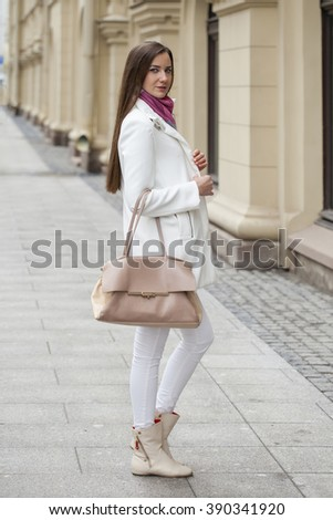 Portrait in full growth the young beautiful woman in white coat on the background of spring street - stock photo