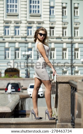Portrait in full growth, Young beautiful blonde woman in beige short dress posing outdoors in sunny weather - stock photo
