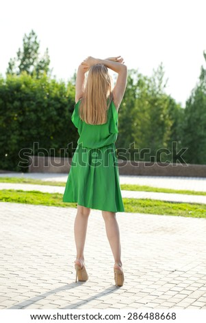 Portrait in full growth, Young beautiful blonde woman in green dress posing outdoors in sunny weather - stock photo