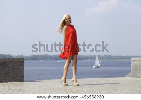 Portrait in full growth, young beautiful blonde woman in red dress, summer city outdoors