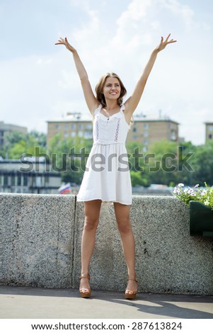 Portrait in full growth, Young beautiful blonde woman in white dress posing outdoors in sunny weather - stock photo
