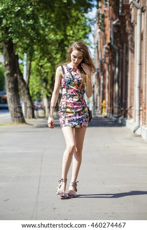 Portrait in full growth, young beautiful brunette woman in sexy dress on the street, summer city outdoors