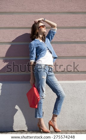 Portrait in full growth, young woman in torn blue jeans on the background wall against the wall - stock photo
