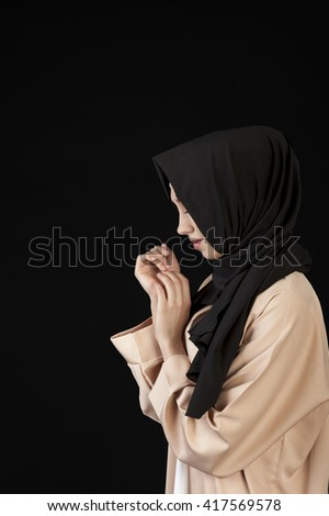 portrait in profile Beautiful Muslim girl in a black scarf on her head on a black background - stock photo