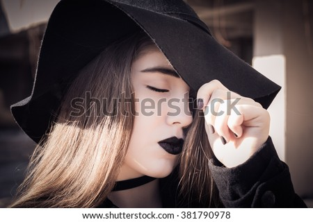 Portrait in profile of a beautiful teenage girl with closed eyes,  black lipstick and black hat close up. Toned effect - stock photo