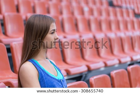 Portrait in profile of a girl at the stadium. - stock photo