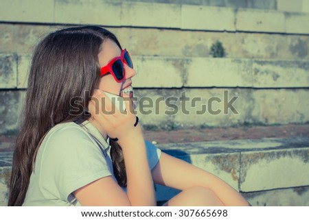 Portrait in profile of a smiling teenage girl in red sunglasses talking on a mobile phone. Toned effect - stock photo
