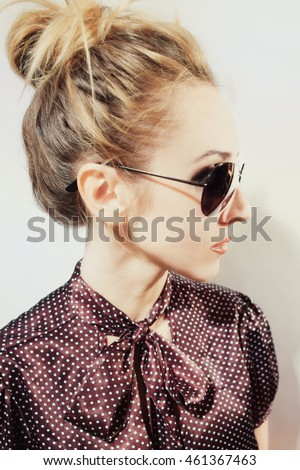 Portrait in profile of beautiful blonde woman wearing sunglasses on white background